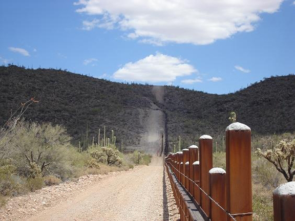 A series of fenceposts marking the boundary with Mexico go off into the distance. A sandy road through the sunny desert runs beside the fence.